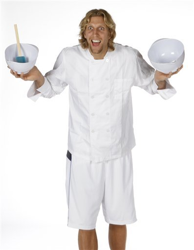 Dirk Nowitzki wears a chefs jacket and holds mixing bowls during NBA basketball media day